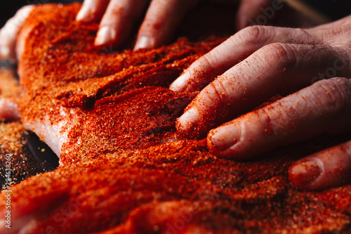 Fototapeta Man preparing raw piece of meat, rubbing different spices and herbs in it before roasting obraz
