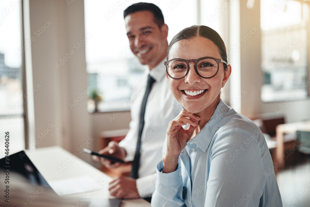 Fototapety, obrazy: Businesswoman smiling while working with a colleague in an offic