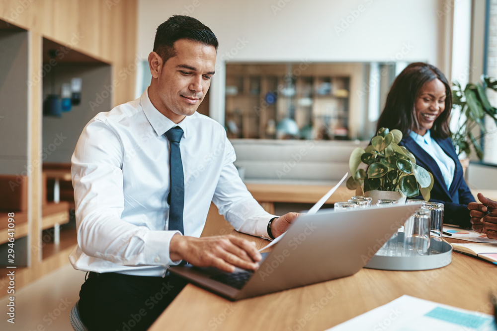 Fototapeta Smiling businessman working on his laptop in a modern office