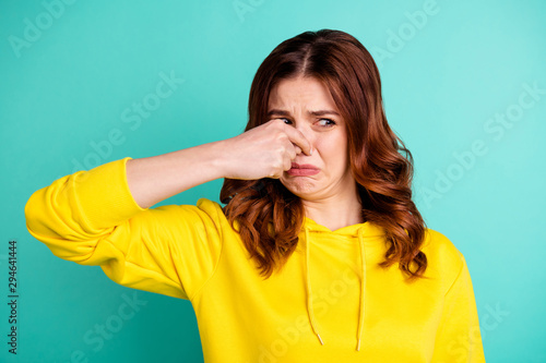 Fotografie, Tablou Photo of disgusted girl smelling something bad nasty looking shutting her nose i