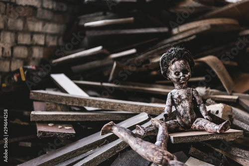 burnt and scary baby doll near damaged toy and wooden boards, post apocalyptic c Wallpaper Mural