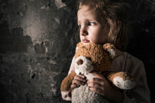 Upset Kid Holding Teddy Bear In Dirty Room, Post Apocalyptic Concept
