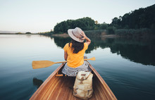 Rear View Of Travel Girl With Hat Paddling The Canoe On Lake
