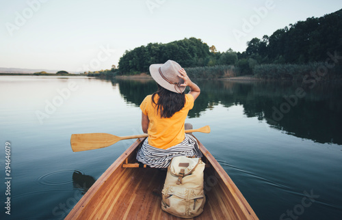 Tableau sur Toile Rear view of travel girl with hat paddling the canoe on lake