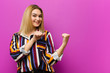 Leinwanddruck Bild - young blonde woman smiling cheerfully and casually pointing to copy space on the side, feeling happy and satisfied against purple wall