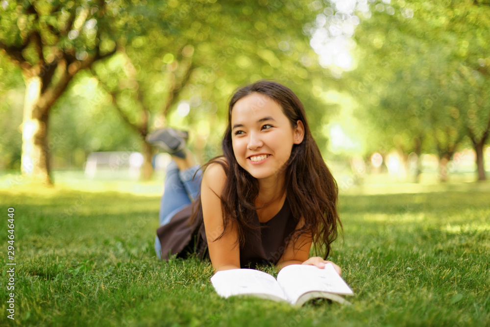 Fototapety, obrazy: Kazakh beautiful girl reading a book in the summer park