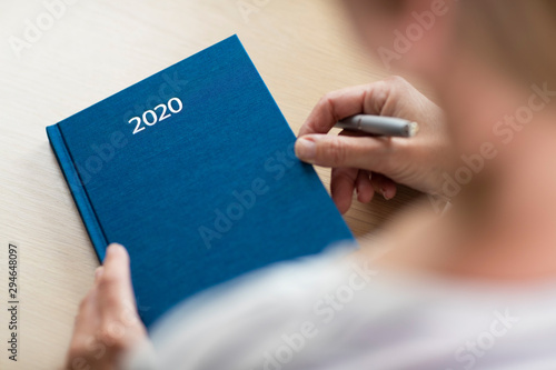 Foto  Close Up Of Woman Opening New Year 2020 Diary On Table