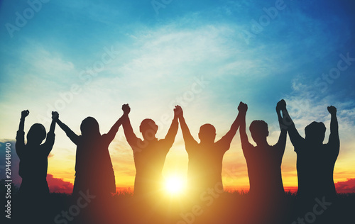 Silhouette of group business team making high hands over head in sunset sky Canvas Print