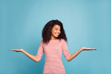 Photo Of Pretty Sales Manager Dark Skin Lady Holding New Low Prices Products On Open Arms Wear Casual Striped Sweater Isolated Pastel Blue Color Background