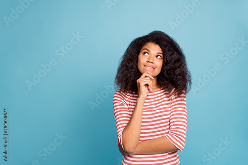 Obraz Photo of serious confused interested black millennial trying to remember important information biting her lips touching chin with hands isolated over blue color vivid background - fototapety do salonu