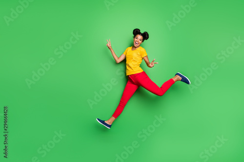 Full body photo of nice dark skin lady jump high running competition participant came first to finish show v-signs wear yellow t-shirt red pants isolated green background