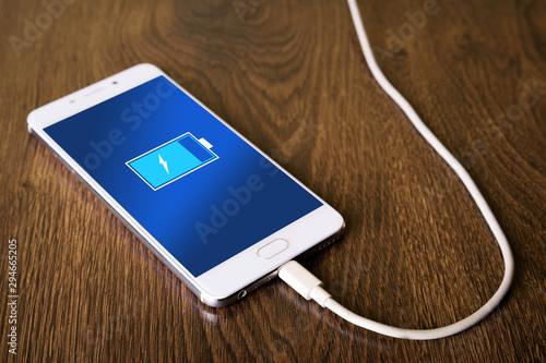 Obraz na płótnie Mobile smart phones,phone charging on wooden desk