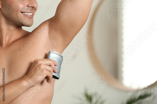 Young man applying deodorant to armpit indoors, closeup Wallpaper Mural