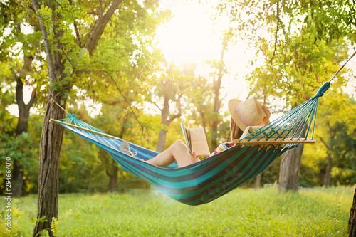 Obraz Young woman reading book in comfortable hammock at green garden - fototapety do salonu