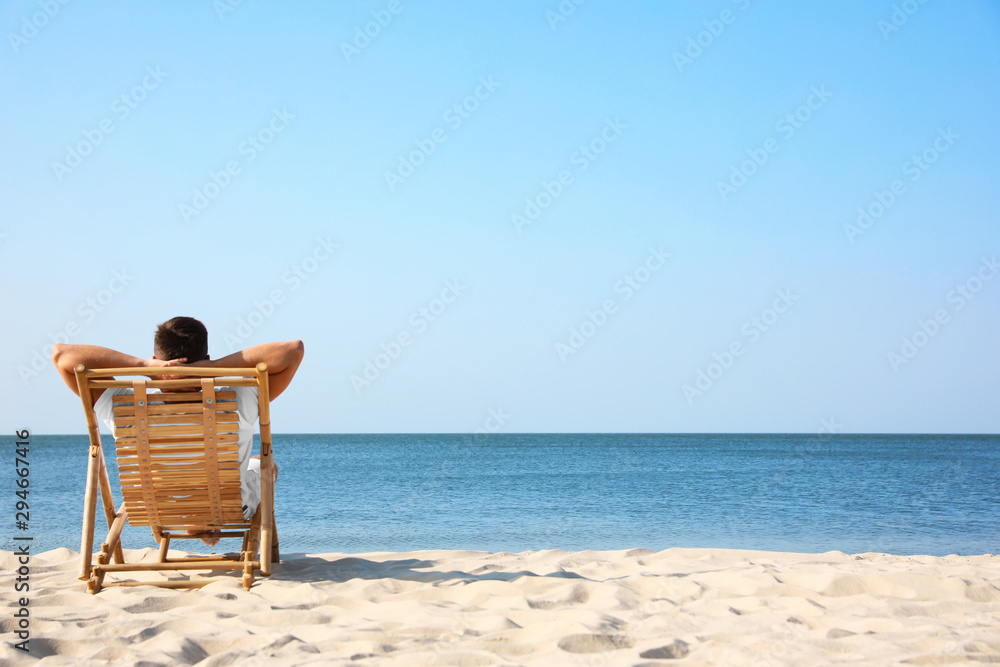 Fototapeta Young man relaxing in deck chair on sandy beach