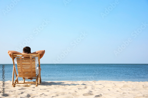 Obraz Young man relaxing in deck chair on sandy beach - fototapety do salonu