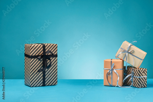 Fotografie, Tablou  Different sizes, colorful, striped and plain paper gift boxes tied with ribbons and bows on a blue surface and background