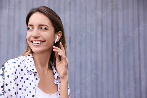 Cuadros en Lienzo  Young woman with wireless headphones listening to music near grey wall