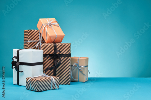 Pinturas sobre lienzo  Different sizes, colorful, striped and plain paper gift boxes tied with ribbons and bows on a blue surface and background
