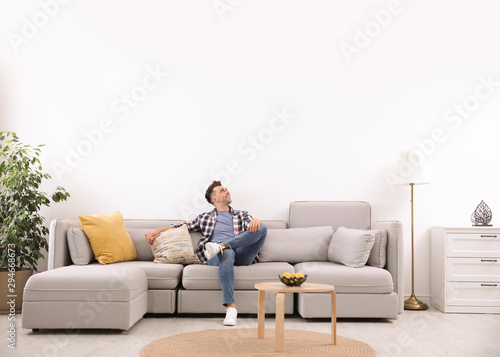 Obraz Young man relaxing on sofa under air conditioner at home - fototapety do salonu