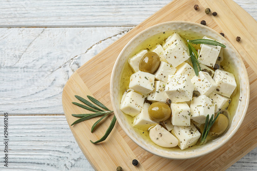 Fototapeta Flat lay composition with pickled feta cheese in bowl on white wooden table obraz
