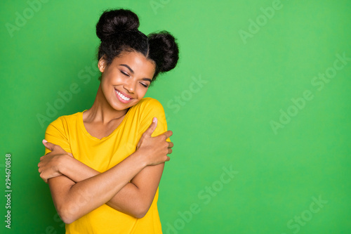 Obraz Just me myself and I. Photo of pretty dark skin lady holding herself in close hugs wear casual yellow t-shirt and red pants isolated green background - fototapety do salonu