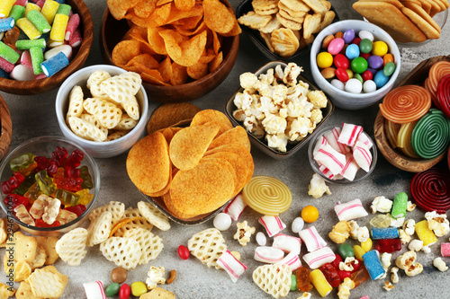 Valokuva  Salty snacks. Pretzels, chips, crackers and candy sweets on table