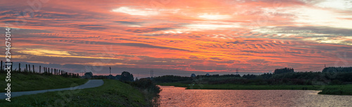 Autocollant pour porte Corail Stunning panorama of dutch landscape with road along the waterside below a vibrant pink sky