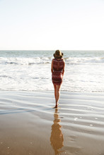 African American Woman Walking In The Wet Sand At The Ocean