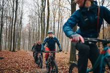 Smiling Mature Woman Mountain Biking With Friends In A Forest