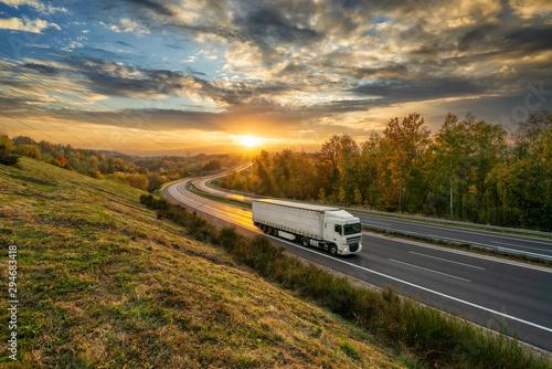 Montage in der Fensternische Landschaft White truck driving on the asphalt highway in autumn landscape at golden sunset with dramatic clouds