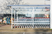 Row Of Supermarket Shopping Trolleys Under Awning On Pavement