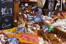 Different Kinds Of French Salami Provencale Presented In Wicker Baskets With Handwritten Chalk Boards On Farmer Market - St. Tropez, France