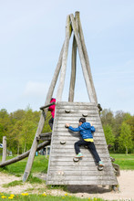 Kid Climbing Wooden Equipment In Playground