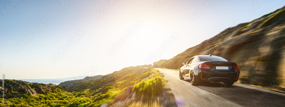 Fototapeta rental car in spain mountain landscape road at sunset