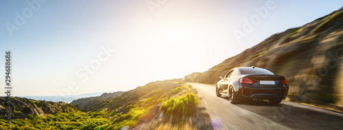 Fototapeta rental car in spain mountain landscape road at sunset obraz