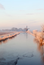 Canal And Old Windmill On Cold Winter Morning