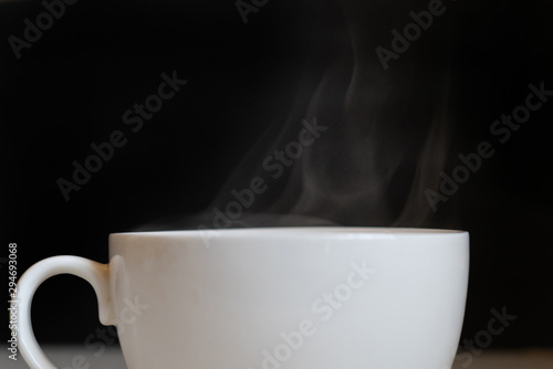 Foto op Plexiglas Chocolade hot steam from the white cup with coffee drink on the dark background