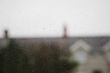 A Rainy Window With Blurry Rooftops And Chimney Pots. The UK.