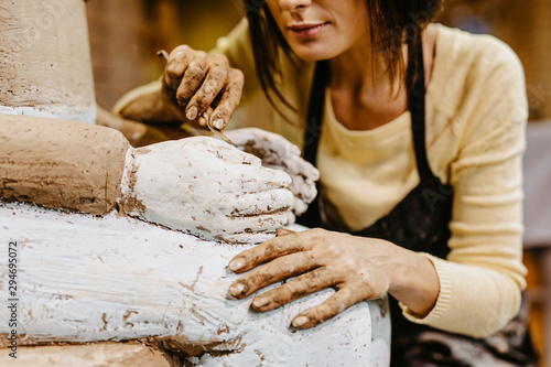 Carta da parati Beautiful middle age woman professional sculptor working on gorgeous sculpture