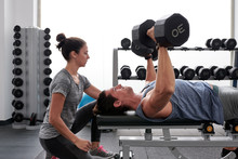 Woman Controlling Man Doing Dumbbell Press On Bench