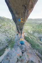 Couple Oudoors, Man Sport Climbing And Woman Taking Photos