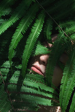Close Up Of Woman's Face Covered With Leaves
