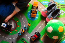 Kid Playing With Toy Cars On Road Map Carpet