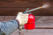 Initial treatment of wooden buildings with a protective coating using a spray gun