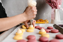 Crop Hand Squeezing Cream On Macarons
