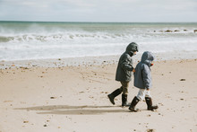 Two Boys Walking Along Beach With Crashing Waves