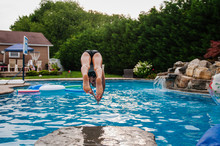 Girl Diving Off Rock Into Pool