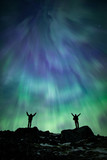 Two people with arms raised watching the aurora borealis in the night sky