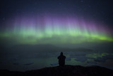 Person overlooking icefjord and icebergs under starry night sky and aurora borealis